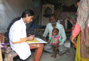 Asha team member examining a child at Seelampur New Area 13 March 2014 (58)