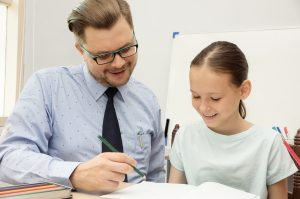 Young teacher and schoolgirl writing in classroom